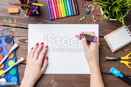 818533812 istock photo Woman's hand drawing on empty sheet of paper. School or art background 818505838
