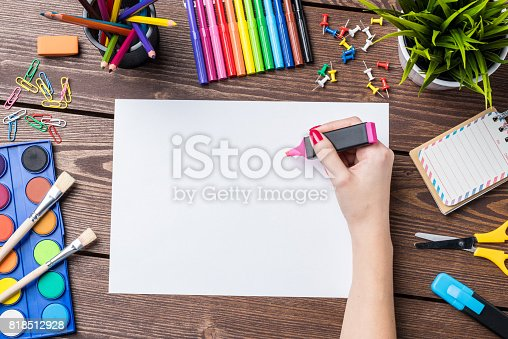 istock Woman's hand drawing on empty sheet of paper. School or art background 818512928
