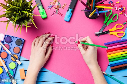 818512928istockphoto Woman's hand drawing on pink paper. School or art background 670915482