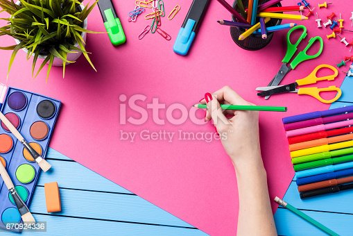 818512928istockphoto Woman's hand drawing on pink paper. School or art background 670924336