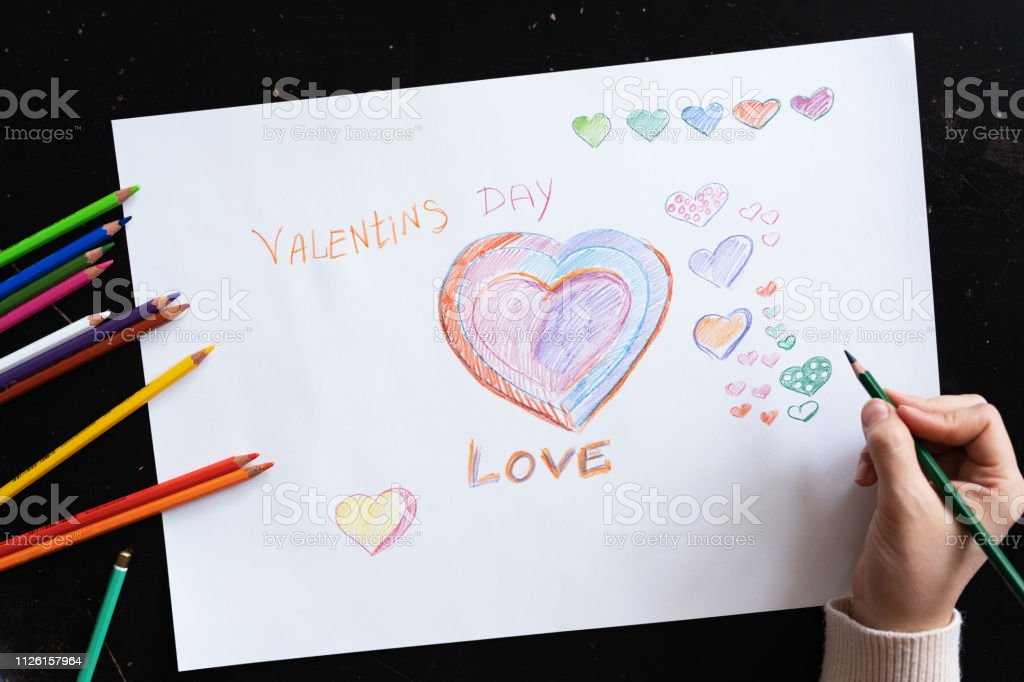woman\'s hand draws pencils hearts on paper for Valentine\'s Day,...