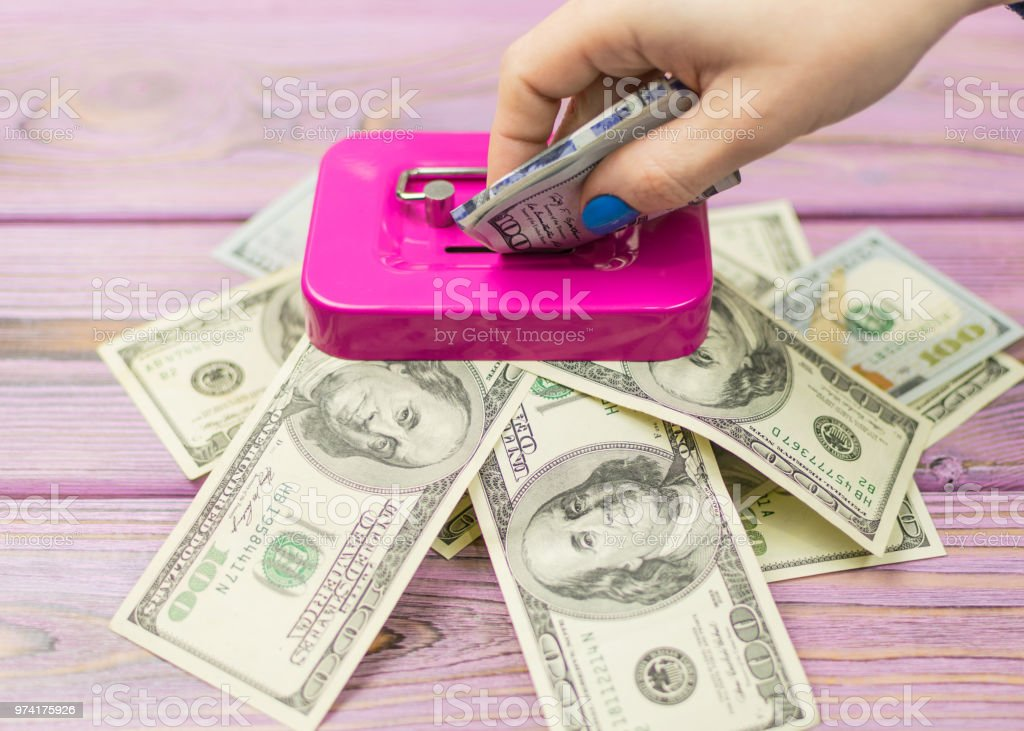 A woman's hand drops dollars into the piggy bank. stock photo