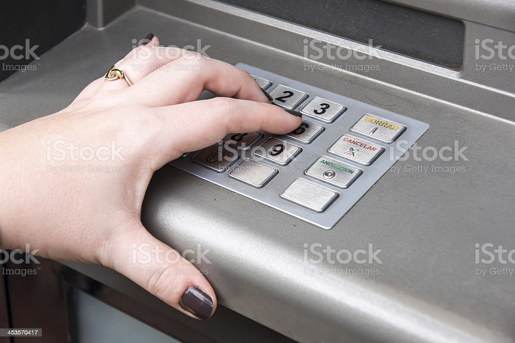woman's hand entering PIN code on ATM machine royalty-free stock photo