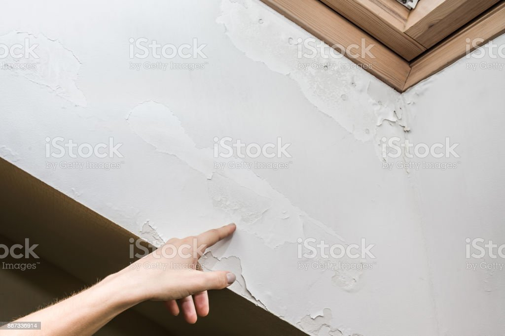 Woman's hand finger pointing to shabby wall defects near the roof window due to humidity problems. stock photo
