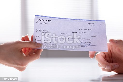 istock Woman's Hand Giving Cheque To Man 1157269239