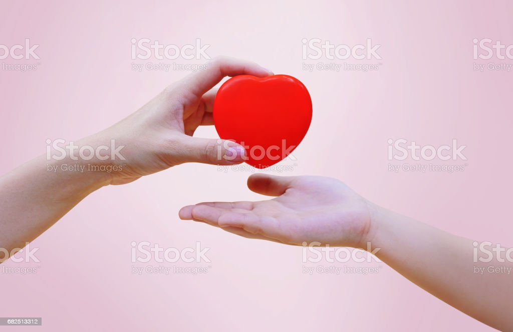 Woman's hand giving red heart to girl kid's hand on pink background, care and share concept with clipping path. Стоковые фото Стоковая фотография