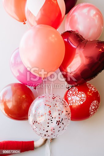 1016084100istockphoto Womans hand (in a red sweater) holding a bundle of colourful balloons (pink, red,crimson) on the grey wall background 936573504