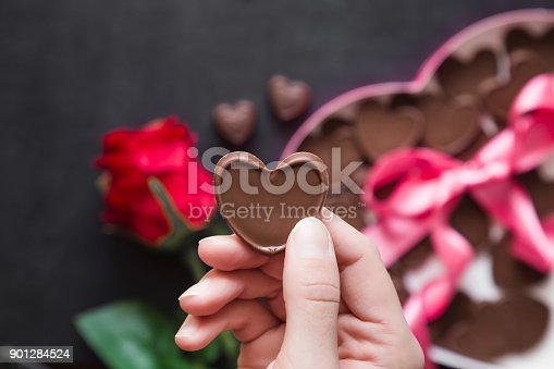 istock Woman's hand holding a chocolate heart. Cute gift from beloved. Red rose with chocolate box of heart shape with pink ribbon on the table. Enjoying sweets. Valentine's day and relationships concept. 901284524