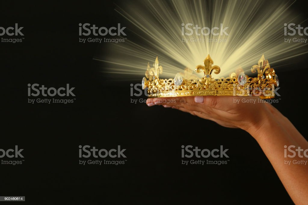Woman's hand holding a crown for show victory or winning first place over black background with glitter overlay. stock photo
