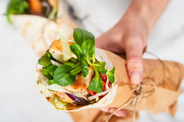 frauenhand hält einen frischen tortilla-wrap runde mit packpapier und schnur gebunden. - veggie wraps stock-fotos und bilder
