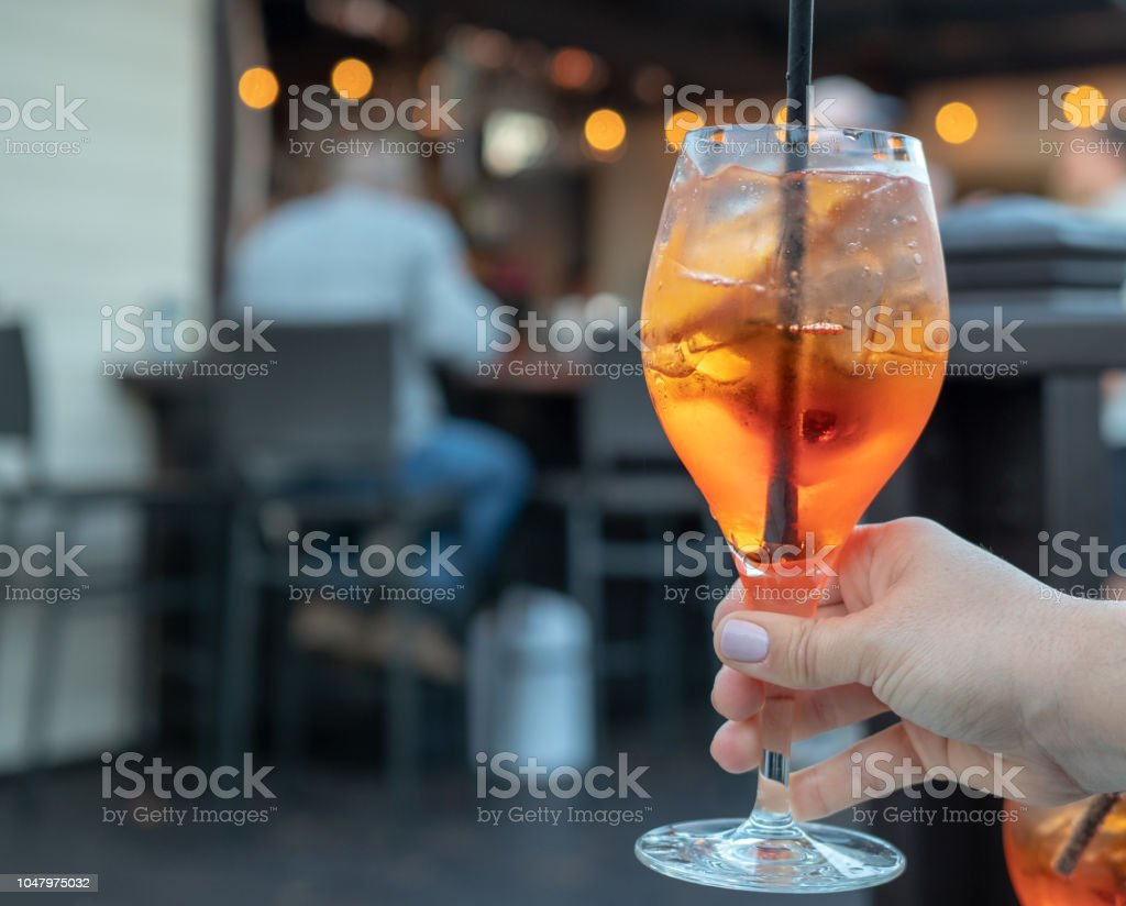 Womans hand holding a full spritz drink at a bar stock photo