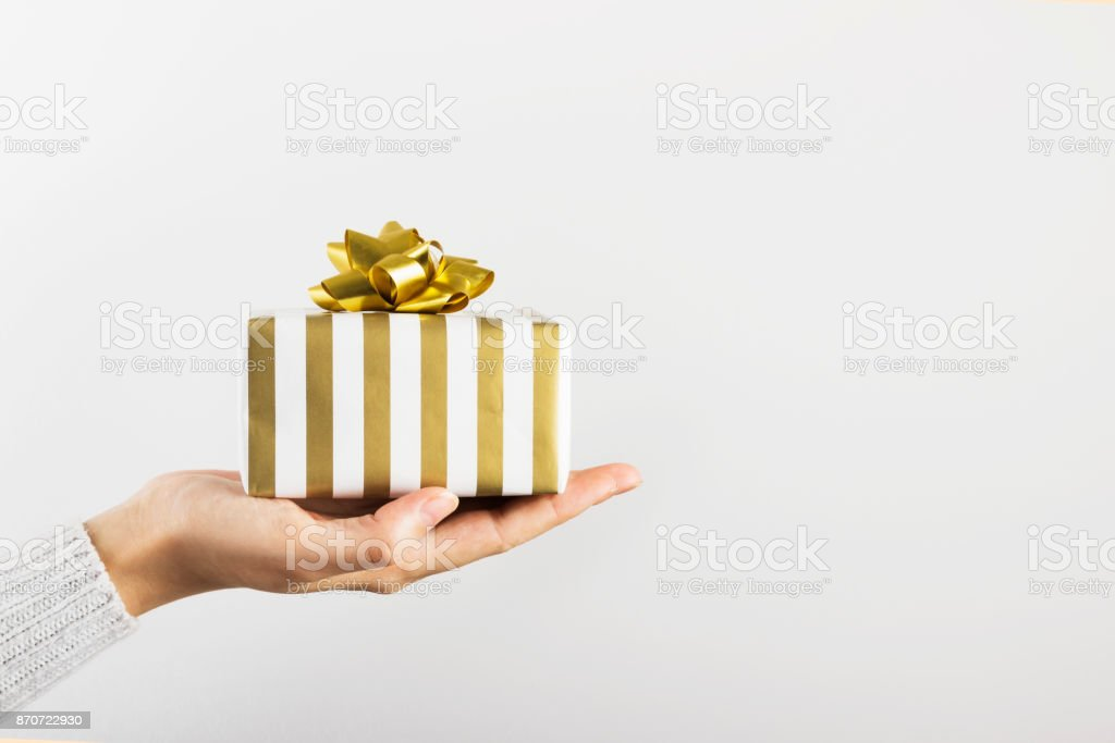 Woman's hand holding a gift in white and gold paper on a gray background. Copy space stock photo