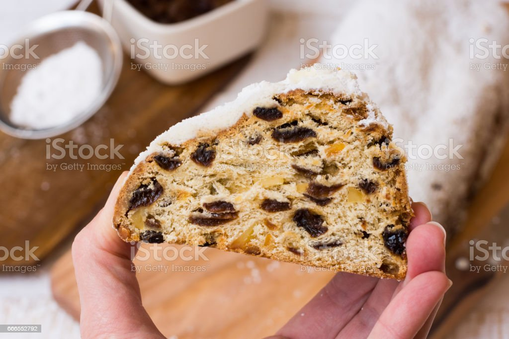 Woman's hand holding a piece of Christmas stollen, loaf and ingredients in background, visible dough texture, close up stock photo
