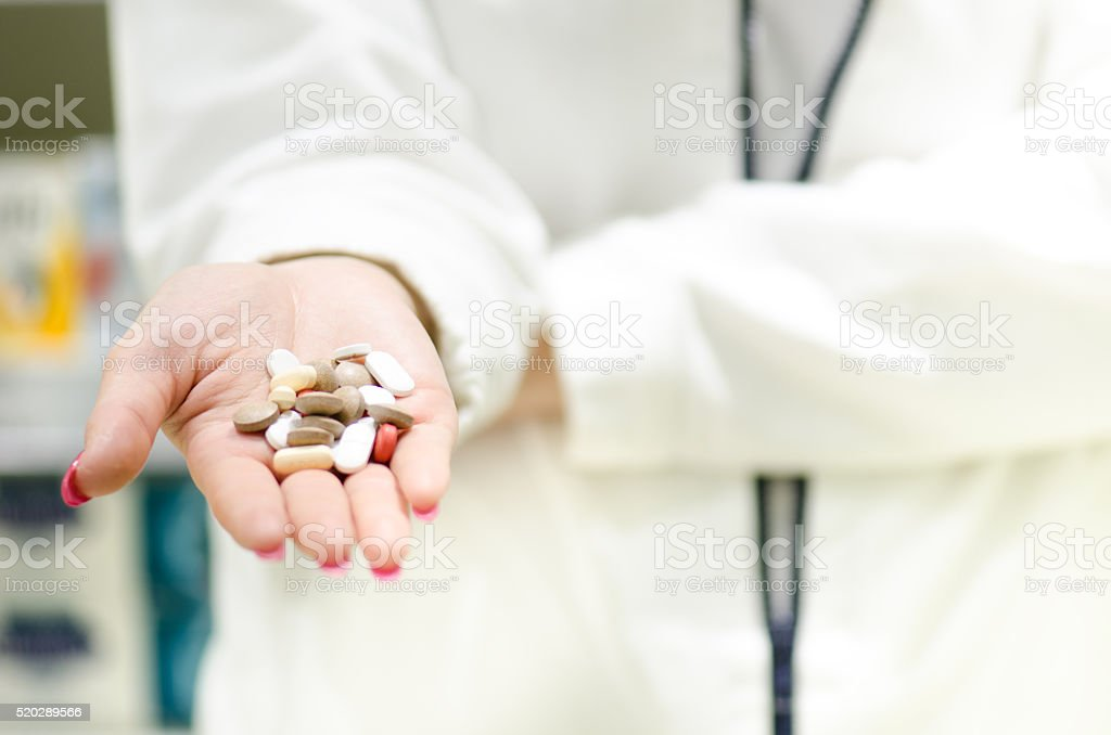 Woman´s hand holding a pills. Pharmacy background. Pharmaceutical and medical stock photo