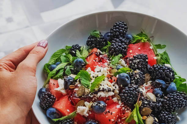 Woman's hand holding a plate with delicious salad with watermelon, arugula and berries stock photo
