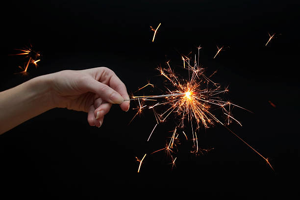 woman's hand holding a sparkler stock photo