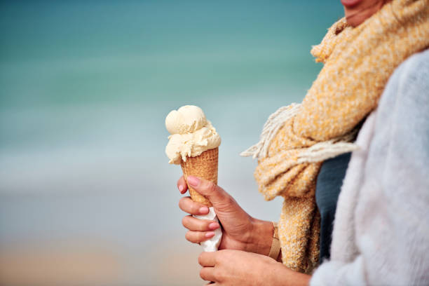 woman's hand holding a vanilla ice cream above fistral beach, newquay, cornwall on an autumn day. - ice cream cone stock pictures, royalty-free photos & images