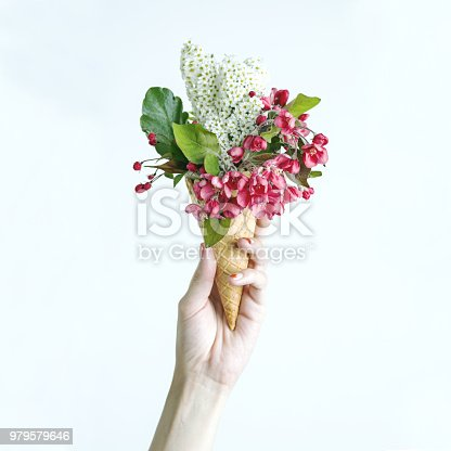680461500 istock photo Woman's hand holding a waffle cone with spring flowers bouquet on the bright background. Flat lay, top view. Mothers day, anniversary, greetings. 979579646