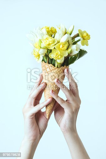 680461500 istock photo Woman's hand holding a waffle cone with spring yellow flowers bouquet on the mint background. Flat lay, top view. Mothers day, anniversary, greetings. 979579828