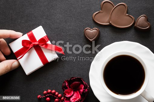 istock Woman's hand holding a white small gift box with red ribbon at the cup of coffee with chocolate hearts on the dark table. Surprise gift from beloved. Romantic atmosphere. Valentines day concept. 889536566