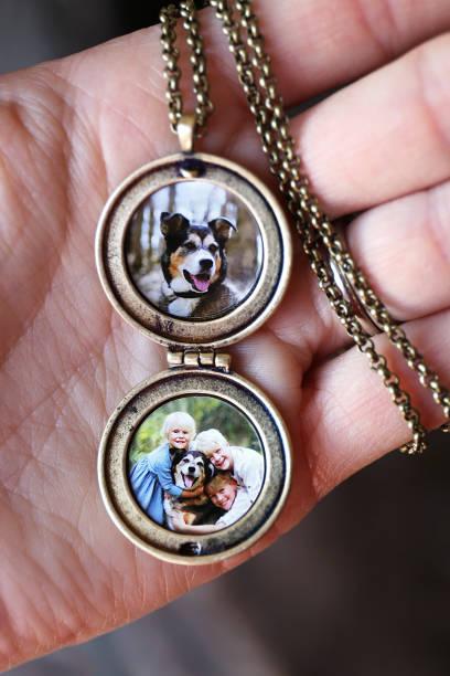 woman's hand holding antique locket with photos of children and pet dog inside - porta retrato imagens e fotografias de stock