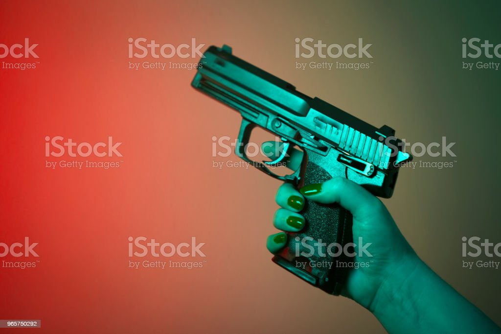Woman's hand holding automatic pistol gun. - Royalty-free Adult Stock Photo
