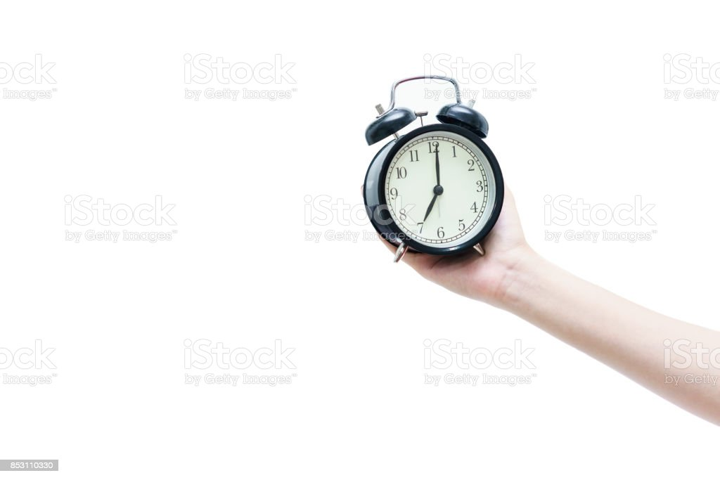 Woman's hand holding black traditional wind-up (keywound), mechanical, spring-driven alarm clock isolated on white background stock photo