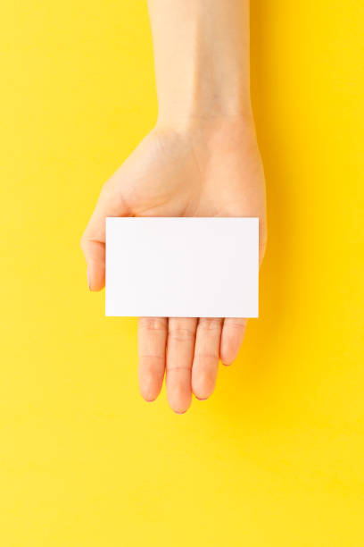 Woman's hand holding business card on yellow background. Mockup. Close up stock photo