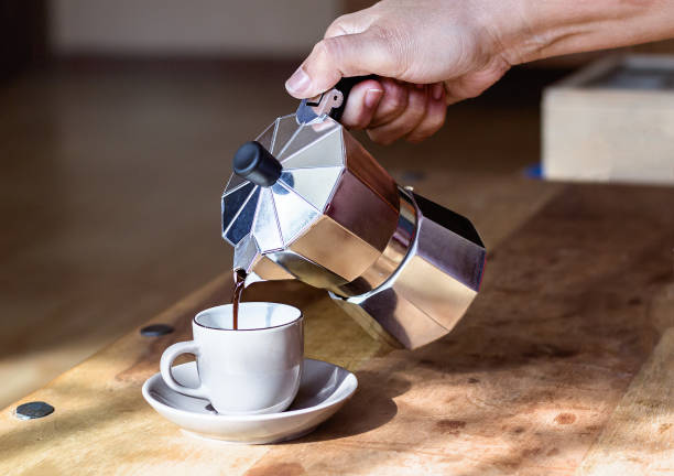 Woman's hand holding coffee maker while pouring coffee on cup Close-up of woman's hand holding metal coffee maker while pouring coffee on cup - Unrecognizable coffee pot stock pictures, royalty-free photos & images