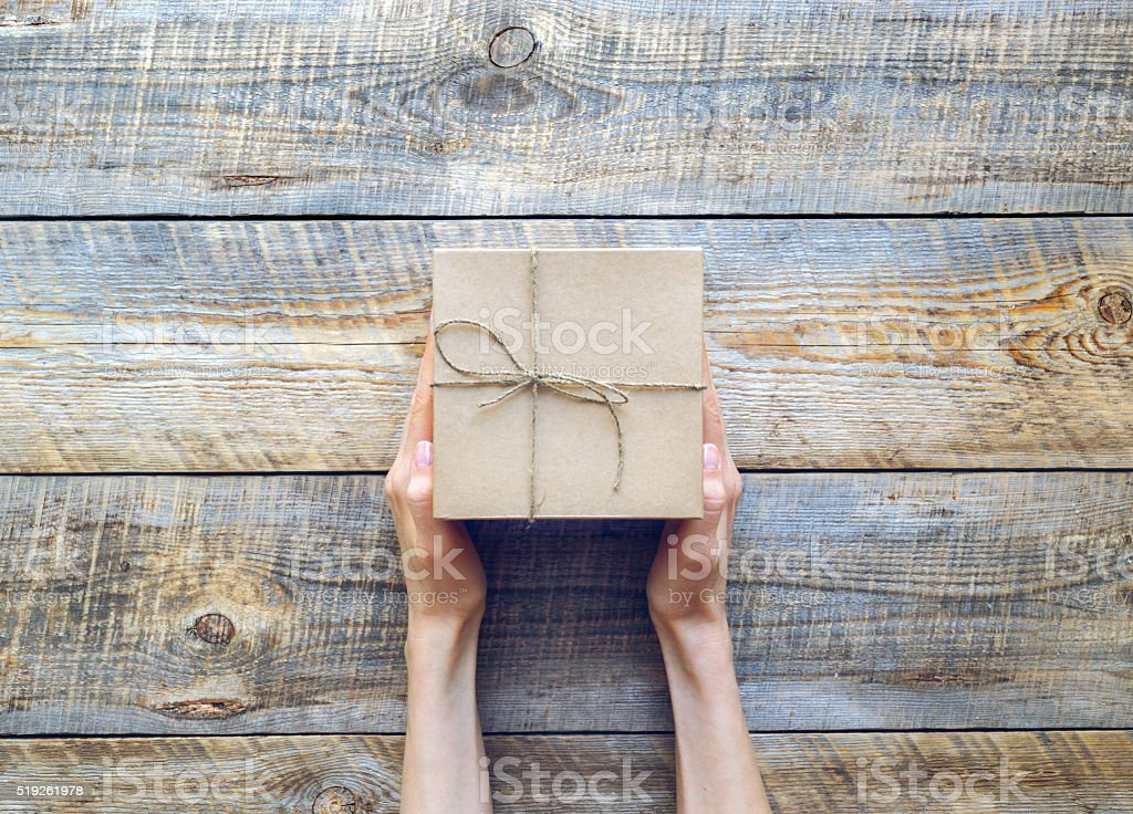 Womans hand holding craft gift box on wooden table