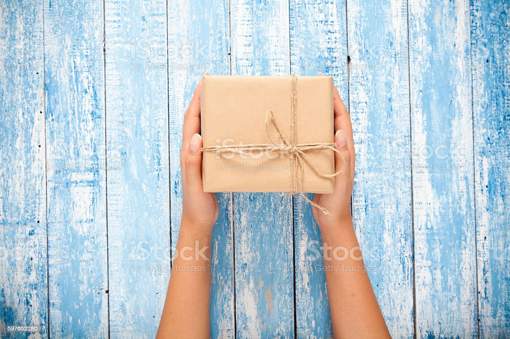Womans hand holding craft gift box on wooden table stock photo