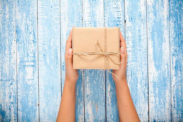 womans hand halten handwerk geschenk-box auf holztisch - bastelkarton stock-fotos und bilder