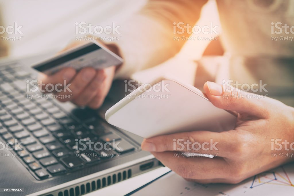 Womans hand holding credit card and smartphone stock photo