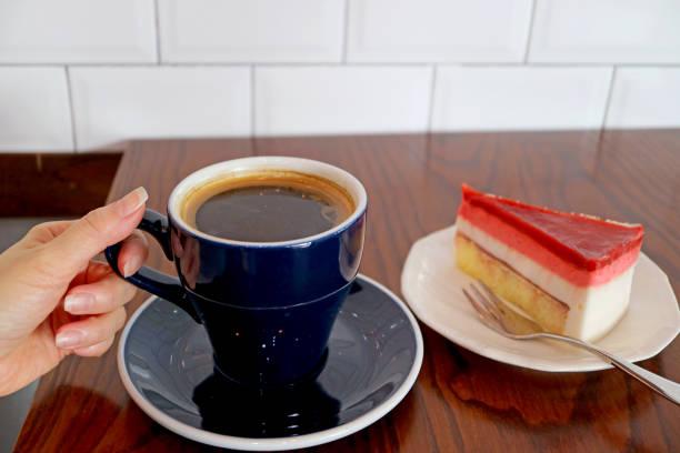 frau hand halten tasse heißen kaffee mit himbeermousse kuchen serviert auf holztisch - marinekuchen stock-fotos und bilder