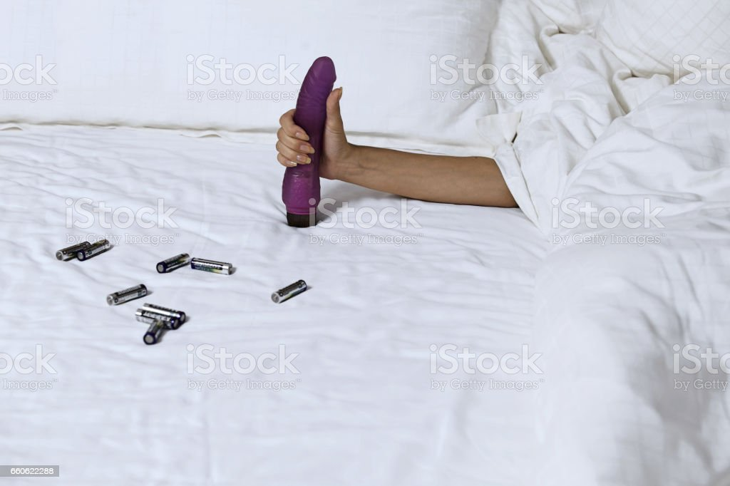 Woman's hand holding dildo in bed stock photo