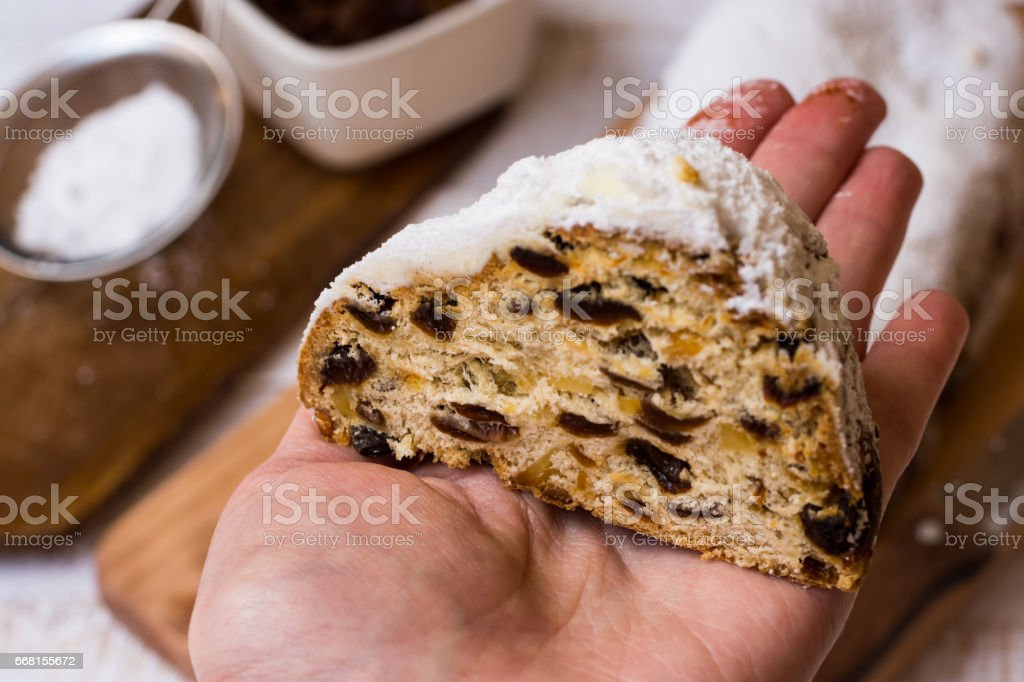 Woman's hand holding end slice of homemade Christmas stollen, ingredients in background, close up stock photo