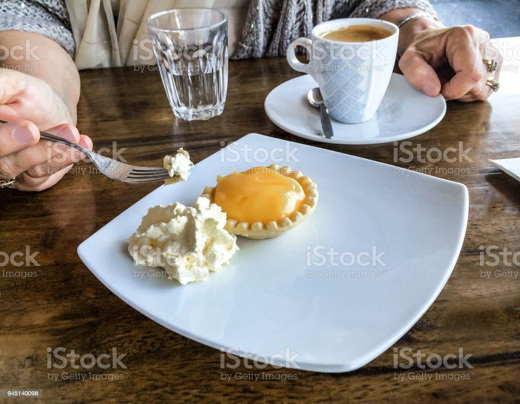 Woman's hand holding fork with bite of Lemon tart and clotted cream -coffee cup setting on table beside plate stock photo