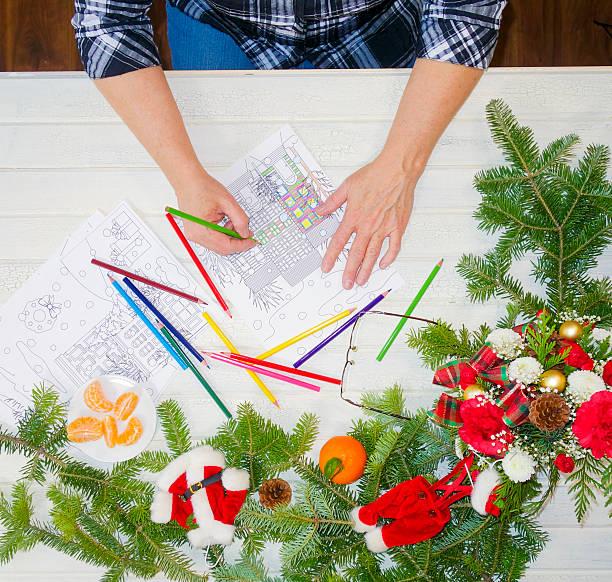 woman's hand holding green pencil crayon coloring a design page - ausmalbilder weihnachtsmann stock-fotos und bilder