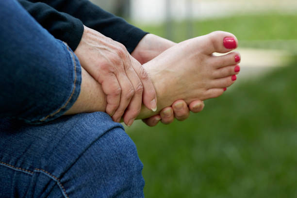 Woman's Hand holding her Foot A woman's hand rubbing the sole of her foot while sitting in a chair outdoors with shallow depth of field rubbing stock pictures, royalty-free photos & images