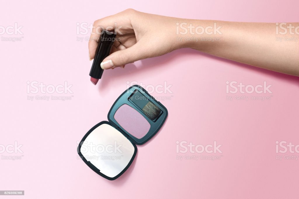 hand holding mirror. woman\u0027s hand holding lipstick next to blush and mirror, top view stock photo mirror