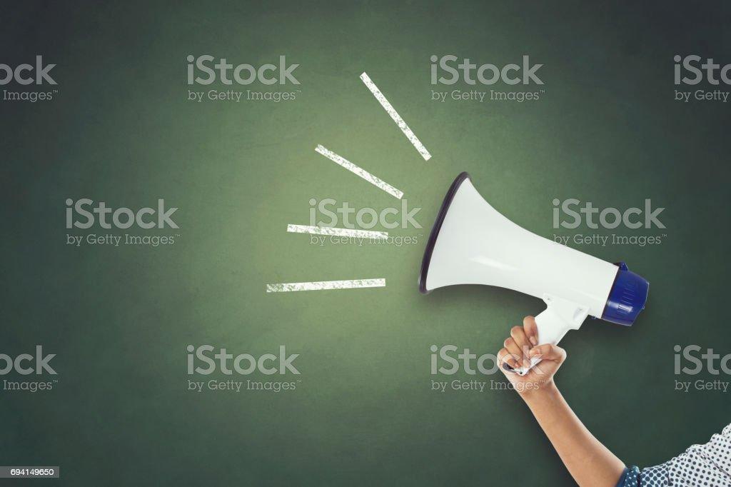 Woman's hand holding megaphone stock photo