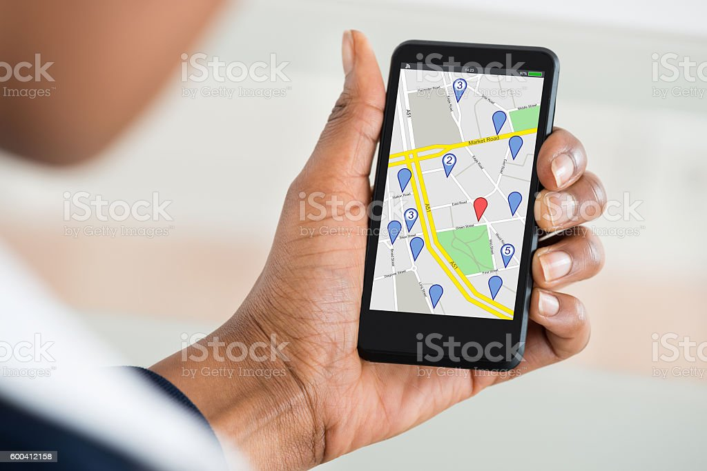womans hand holding mobile phone with location mark on map stock photo more pictures of adult. Black Bedroom Furniture Sets. Home Design Ideas