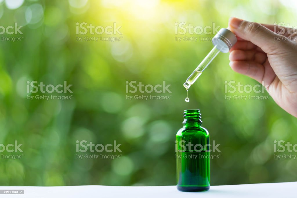 woman's hand holding Pipette , essential liquid falling into glass. stock photo
