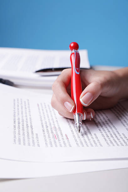 Woman's hand holding red pen proofreading a paper
