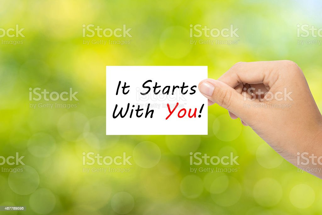 Woman's hand holding sign that reads it starts with you stock photo
