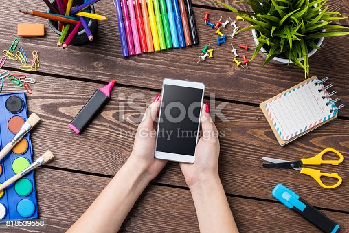 818533812 istock photo Woman's hand holding smart phone. School or art background 818539558