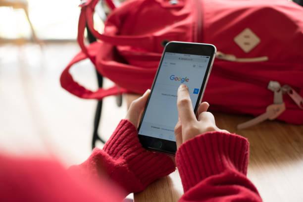 zarte Frauenhand holding Smartphone und Verwendung von Google-Website für die Suche nach Daten – Foto