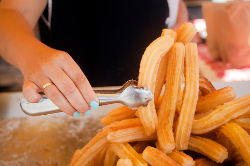 Close-up view of woman's hand holding some churros with cooking pliers over heap of them on a tray. Outdoors market stall.