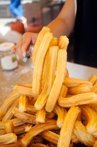 Close-up view of woman's hand holding some churros with cooking pliers over heap of them on a tray below, in a outdoors market stall.