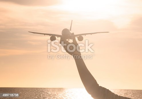 close up photo of woman's hand holding toy airplane in sunset